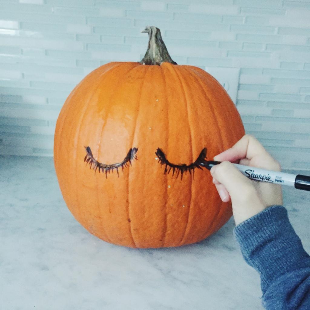 drawing eyelashes on a pumpkin