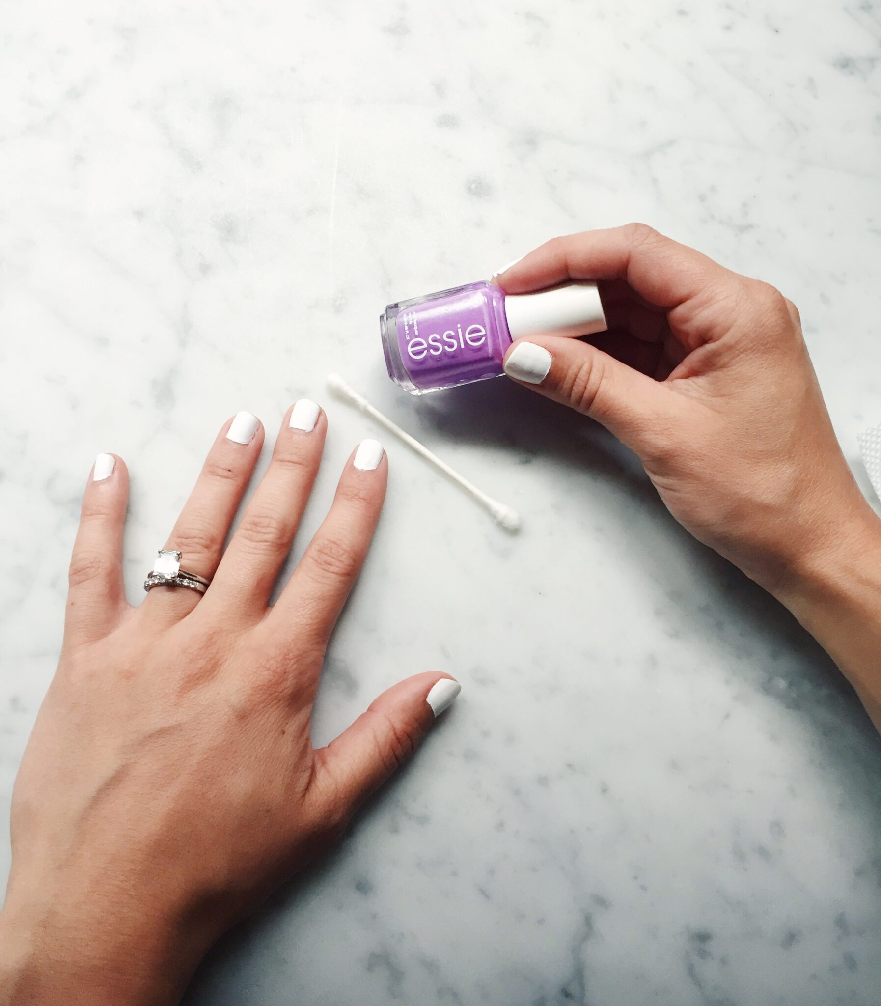 white base nail polish with essie purple nail polish and a q tip