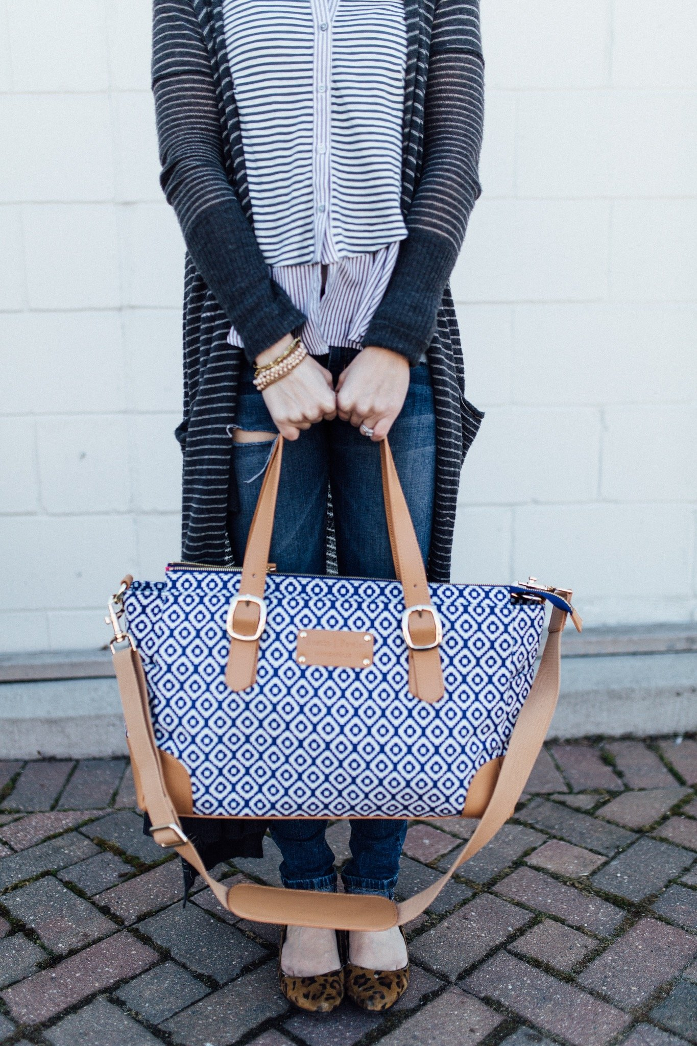 Holding a classy organized diaper bag by minneapolis brand austin fowler in long free people sweater and leopard flats.