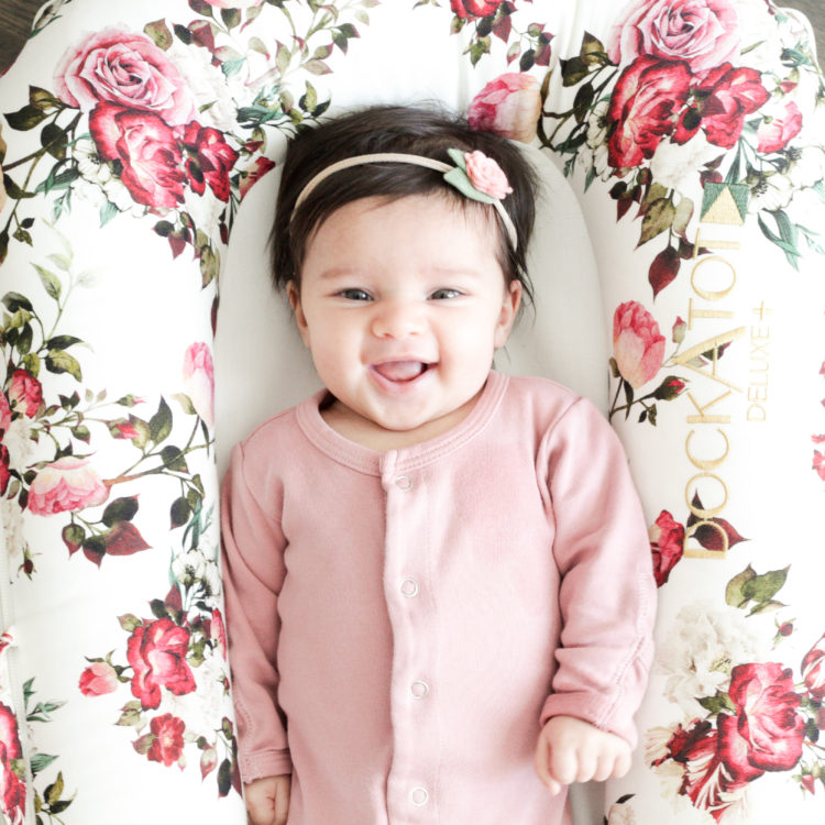 A happy newborn baby girl in a floral dockatot deluxe.