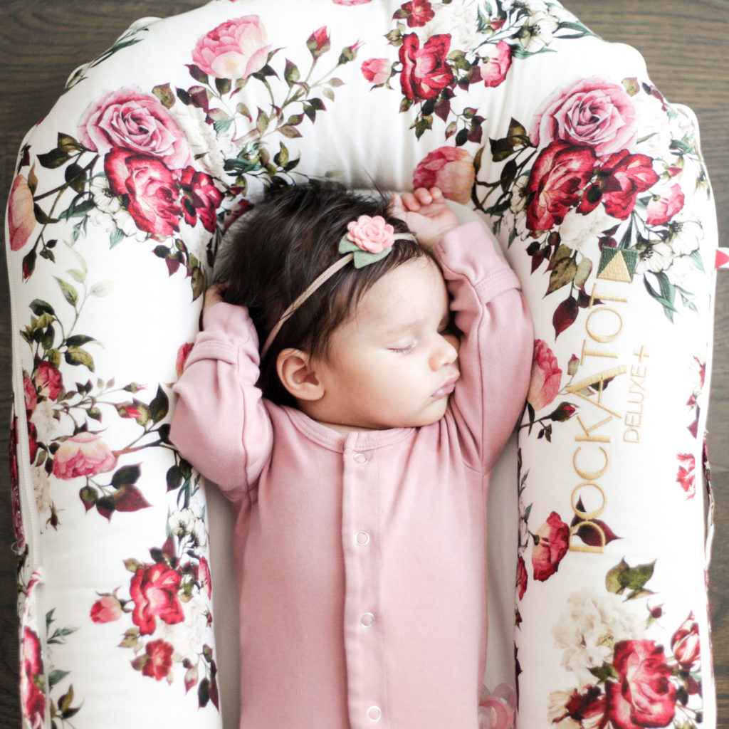 Newborn baby girl sleeping in a floral dockatot deluxe.