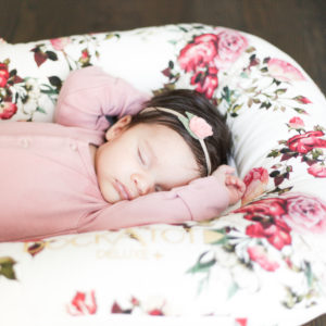 Newborn baby girl sleeping in a floral dockatot deluxe with a floral headband.