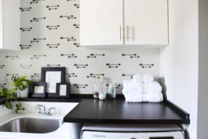 Laundry room decor featuring a faux arrow wallpaper accent wall with stacked white towels.