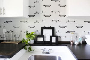Laundry room decor featuring a faux arrow wallpaper accent wall.
