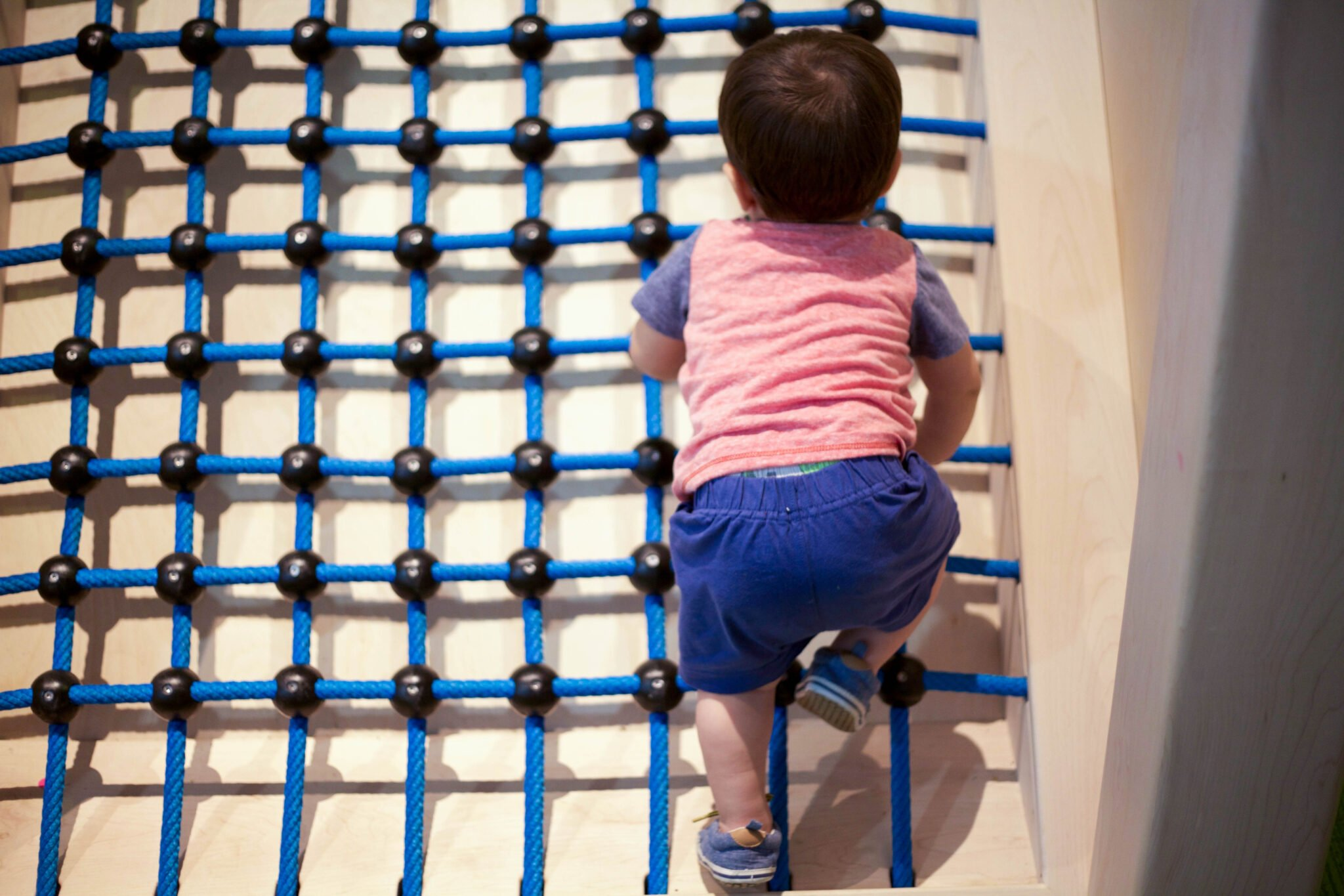 Climbing a rope ladder at a minnesota children's museum toddler section