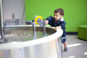Playing in the water at the minnesota children's museum toddler section in a rain jacket.