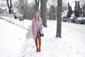 fun in the snow in a pink sweater jacket, tan over the knee boots and fair trade leather bag