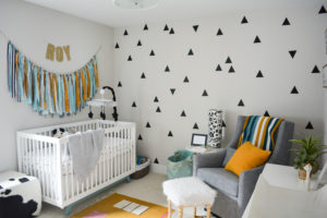 modern gender neutral nursery with triangle accent wall and fabric wall hanging
