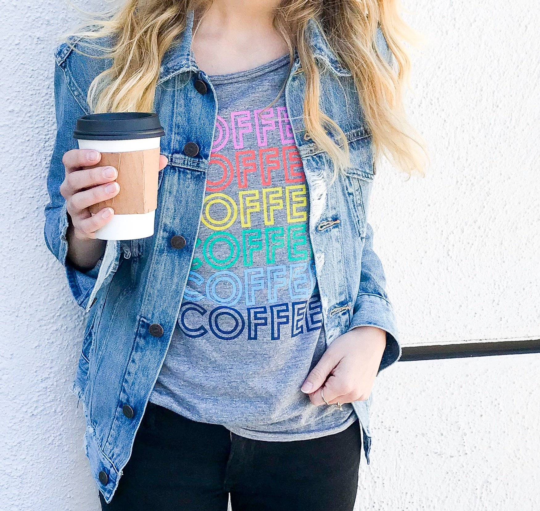 Casual spring outfit - coffee graphic tee, distressed denim jacket and black denim.