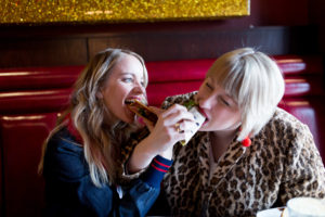 Cofounders of mix like a mother, Michelle Raven and Jen Biswas, sharing a taco.