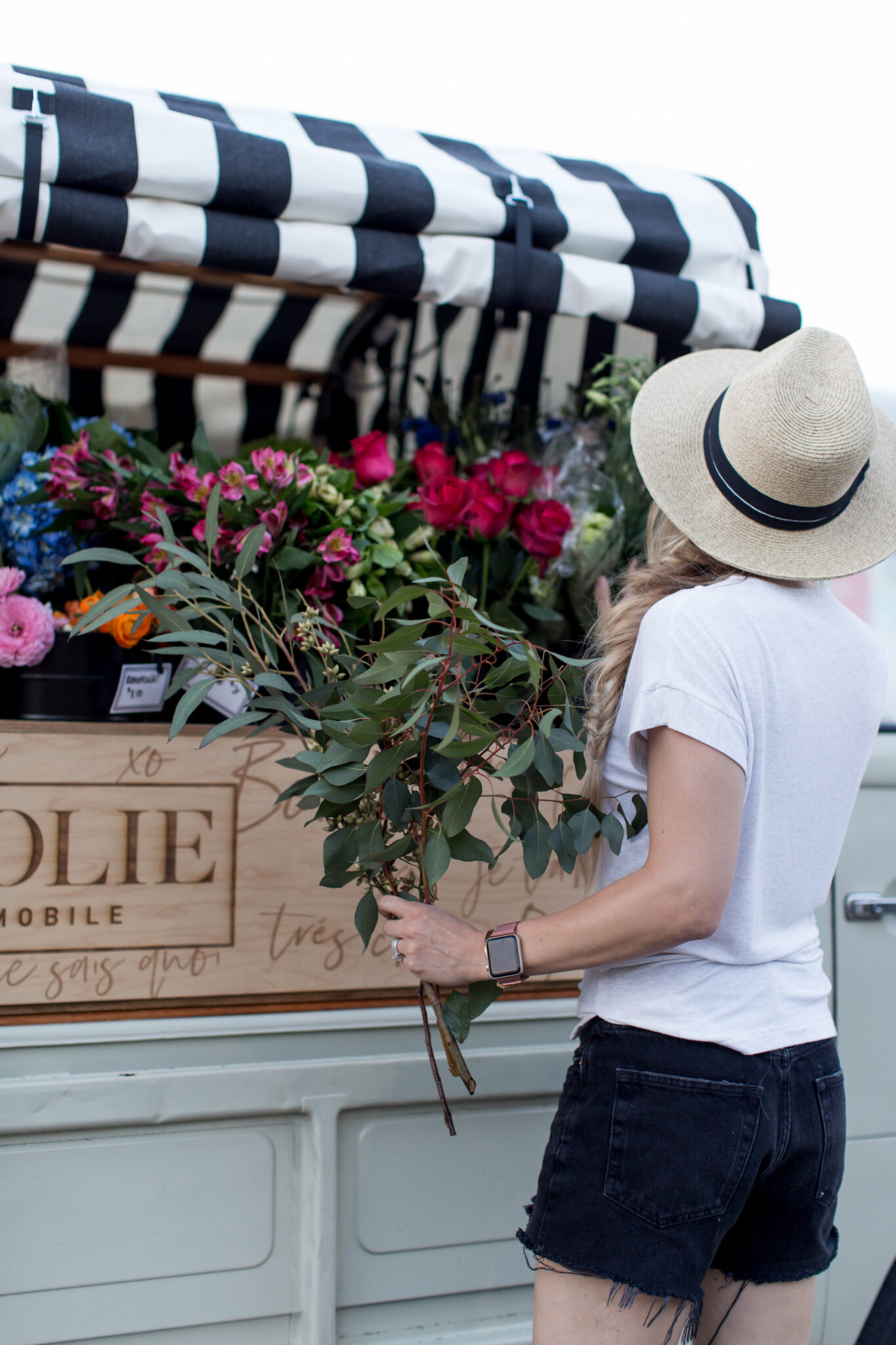 picking flowers from a flower truck in black cut off shorts, white tee and straw hat
