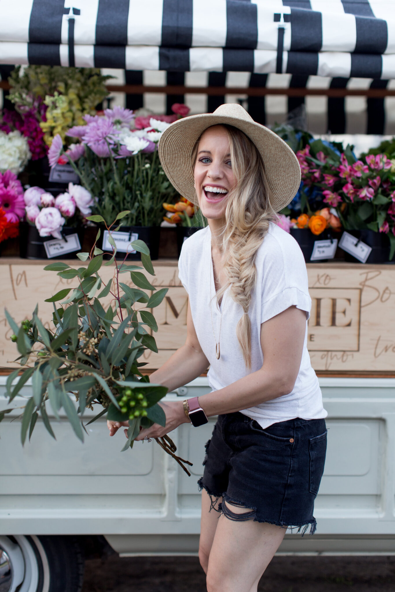 summer outfit for a casual day. blonde girl with fishtail braid and straw hat in front of majolie flower truck in black shorts, white top and black peep toe shoes