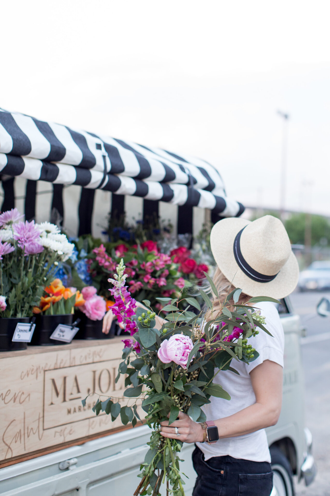 picking a summer bouquet of snap dragon and peony in a straw hat, cut offs and white tee