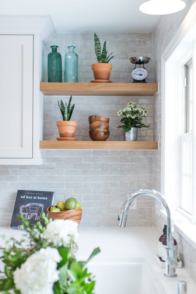 white kitchen with floating shelves and plants in terra cot pots