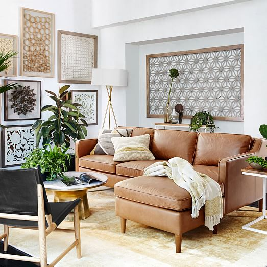 neutral living room with leather couch, gold and white pedestal coffee table and plants