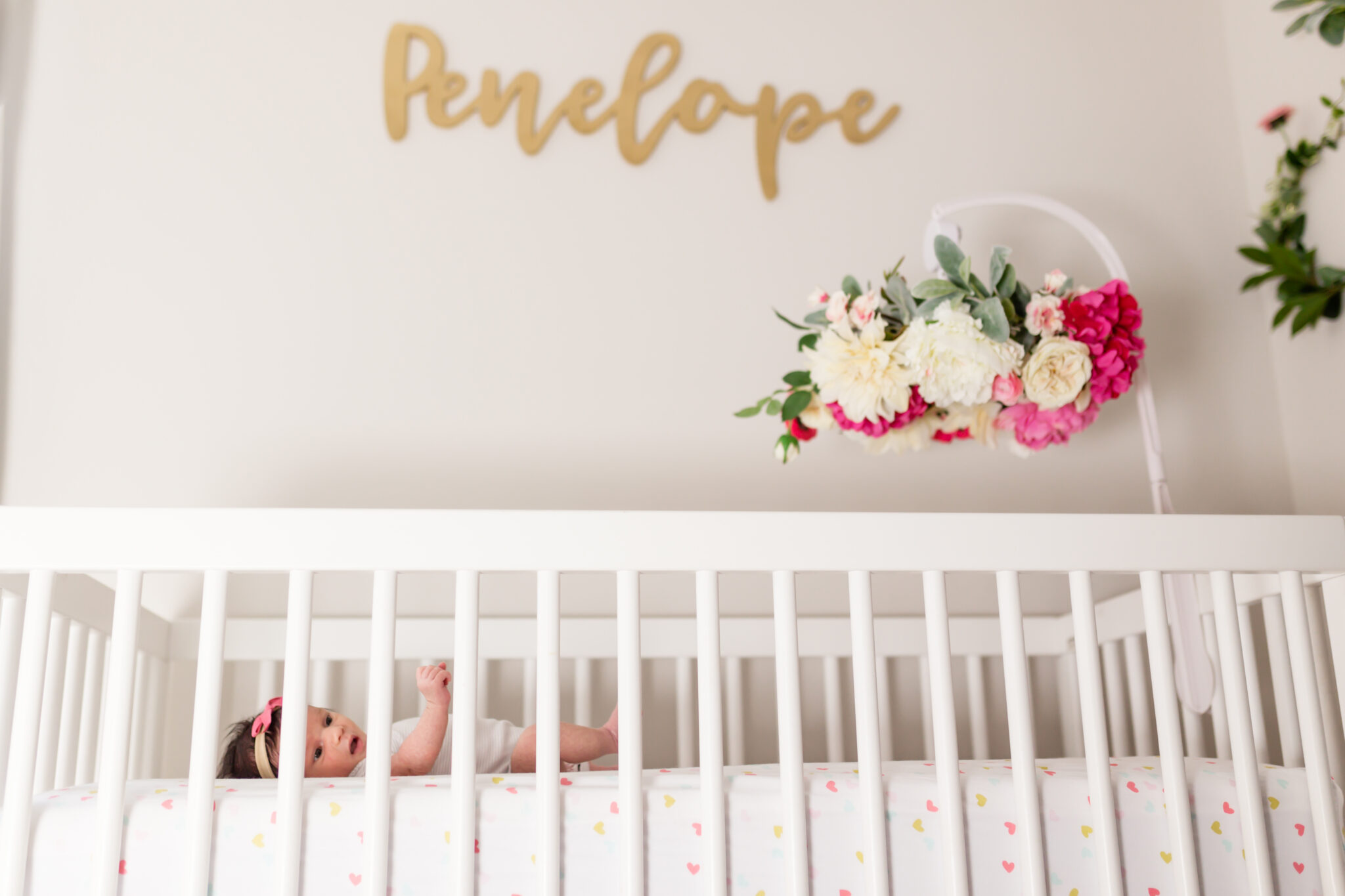 Penelope name out of wood in nursery with floral mobile