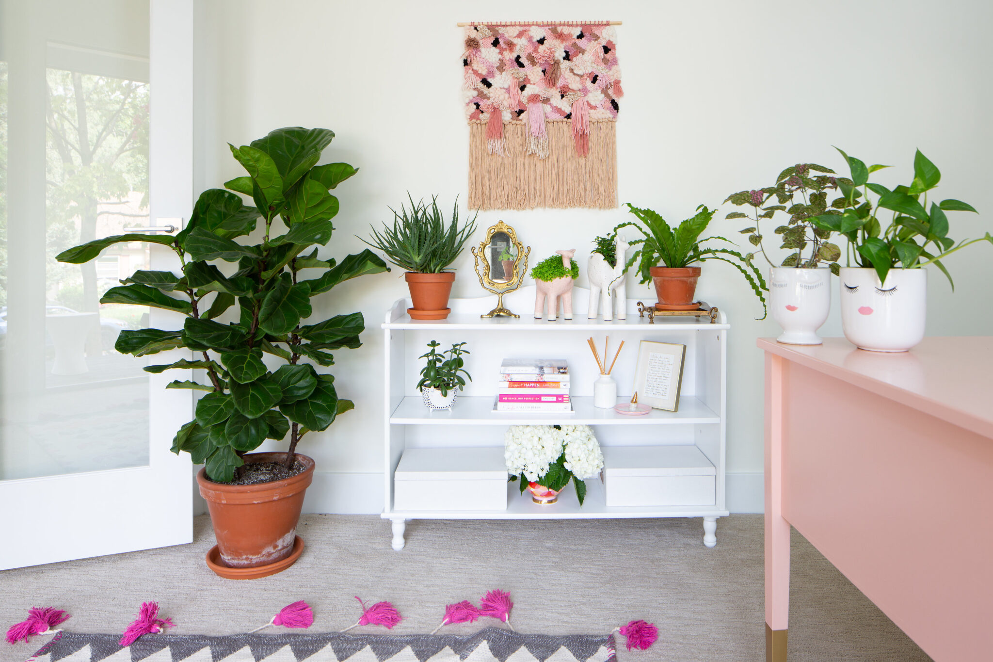 feminine home office with weave, fiddle leaf fig plant and pink accents