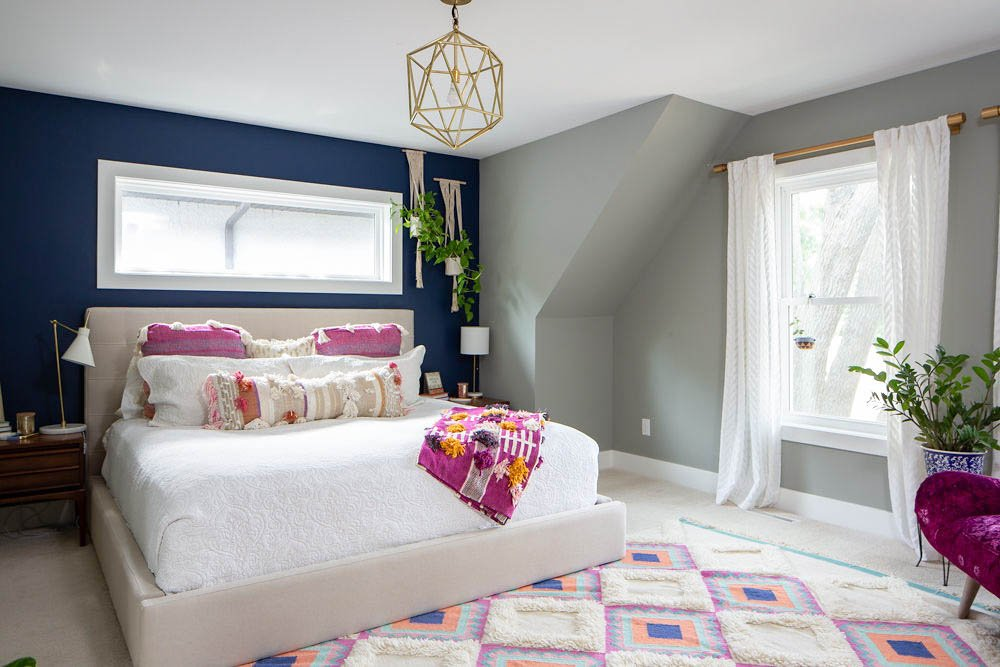 Bright Navy Accent Master Bedroom - an Anthropologie inspired bedroom with gold lights, navy accent wall, fuchsia a