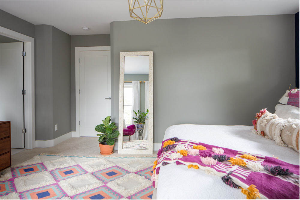 Bright master bedroom with West Elm mirror and fiddle leaf fig