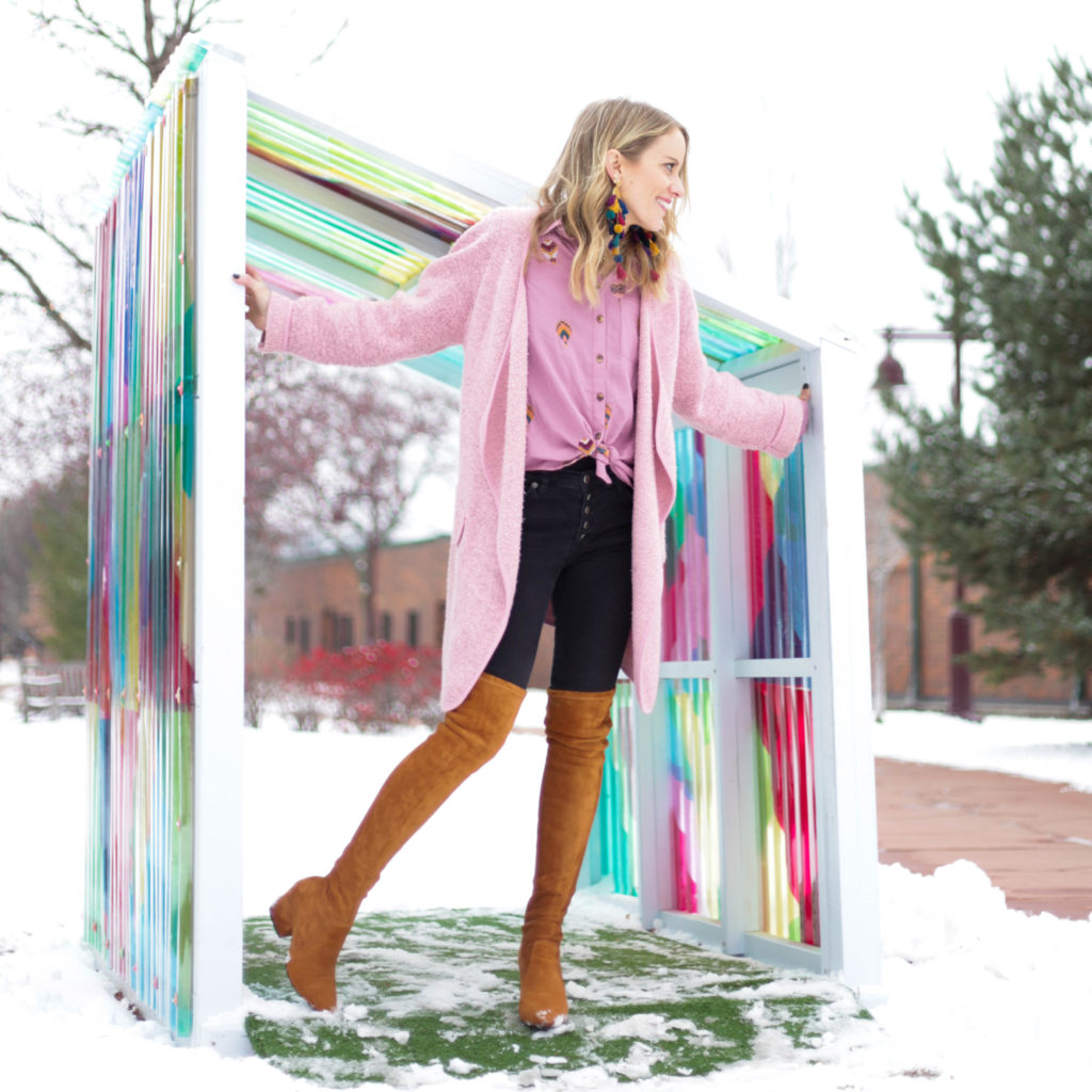Dress down thigh high boots with oversized sweaters like this pink cardigan.
