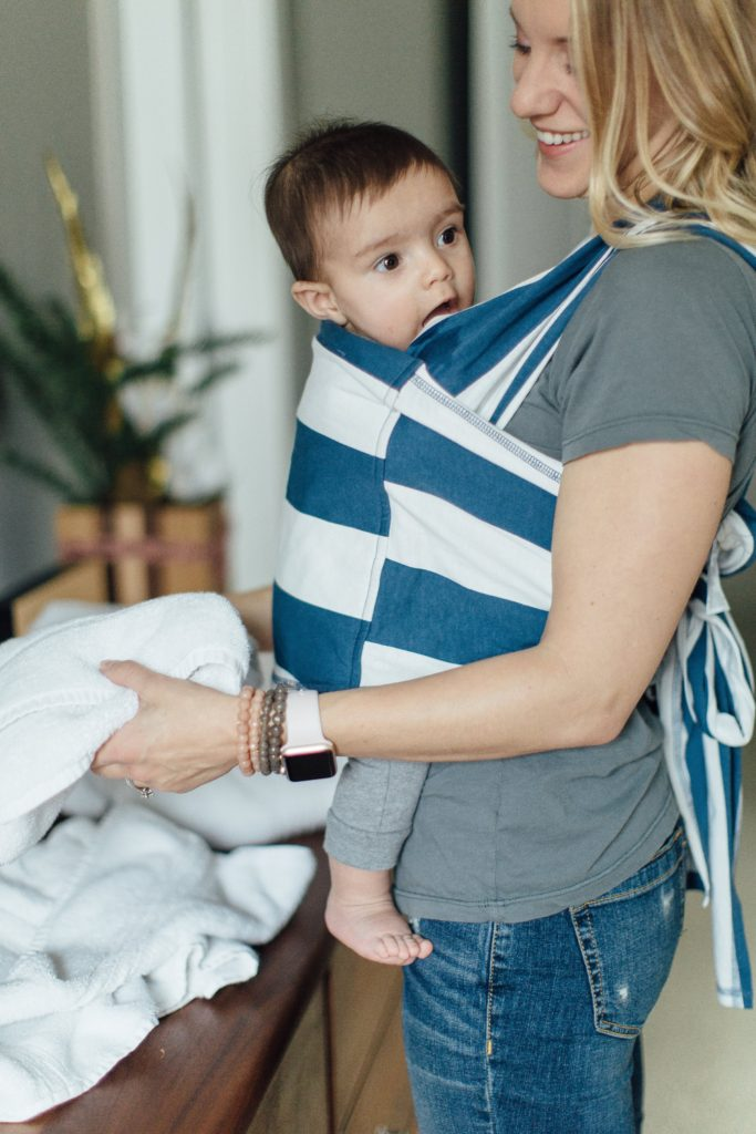 An easy to wear, easy to use baby carrier in blue and white stripes.