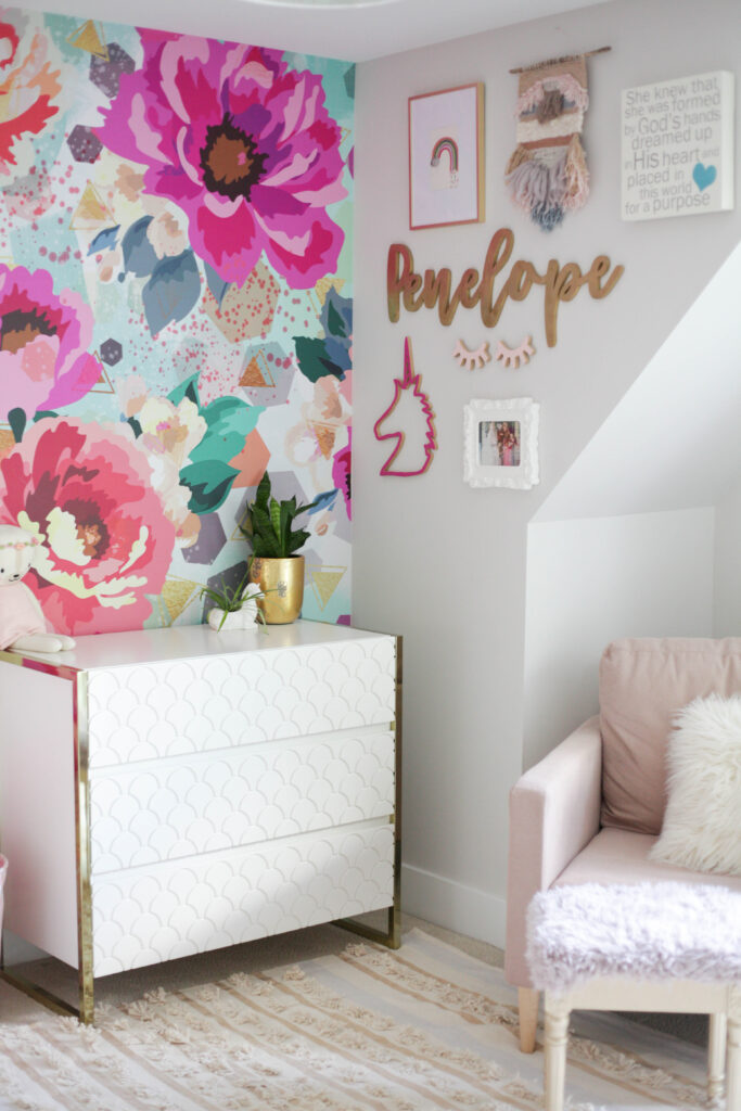 bright and bold floral wallpaper with fun gallery wall and white and gold dresser