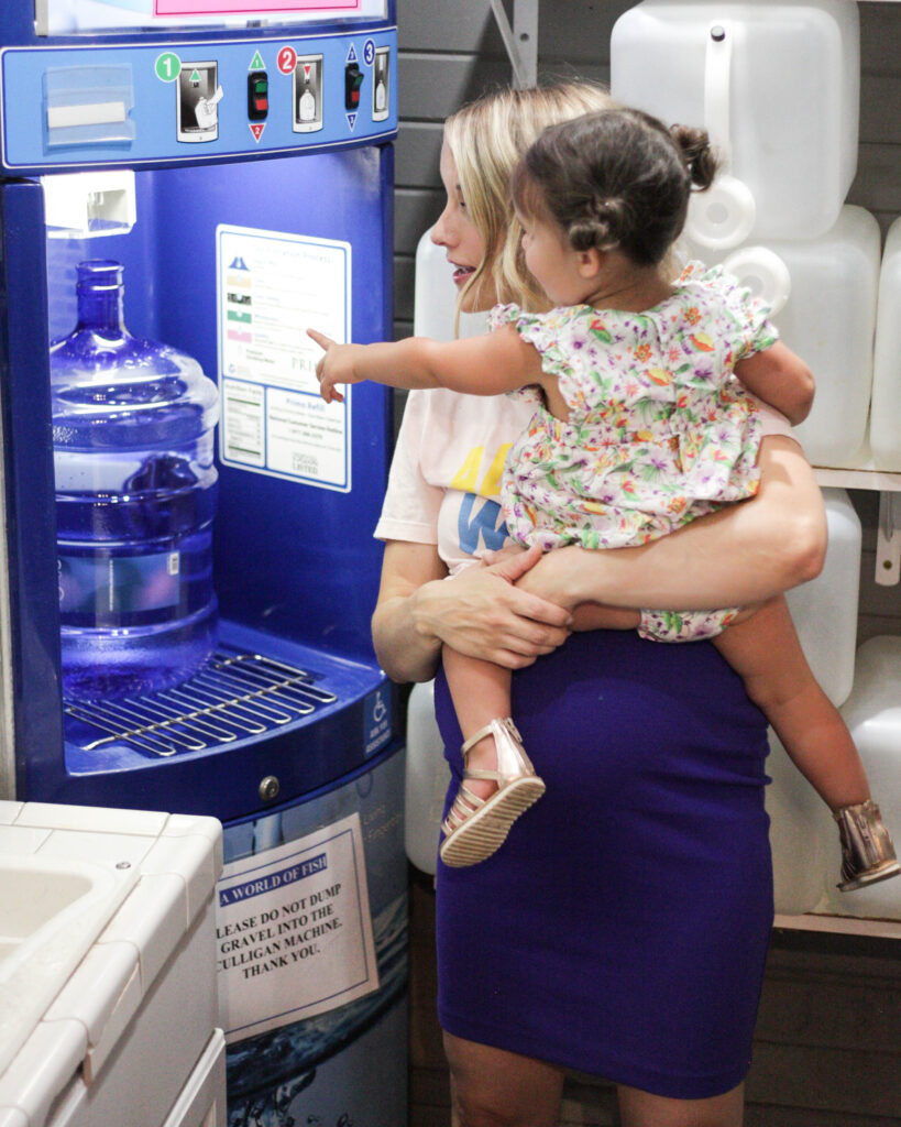 Using a dispenser to fill up a Primo water bottle
