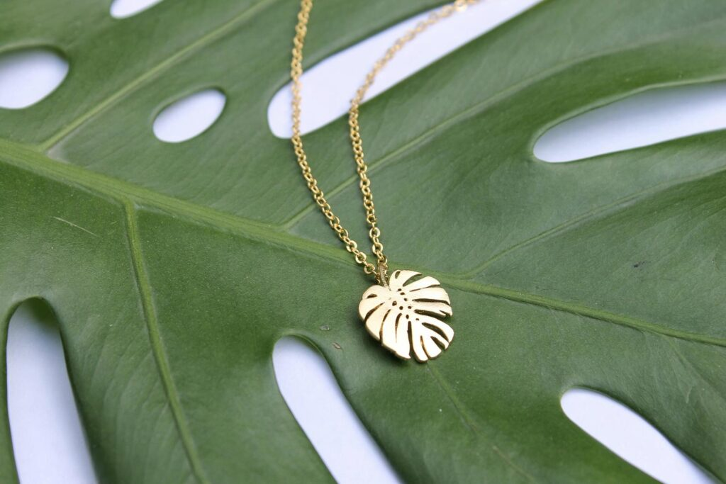 A dainty, gold ostera leaf plant necklace.