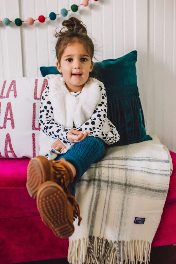 Black and white girls dress with furry vest over it and blue leggings.