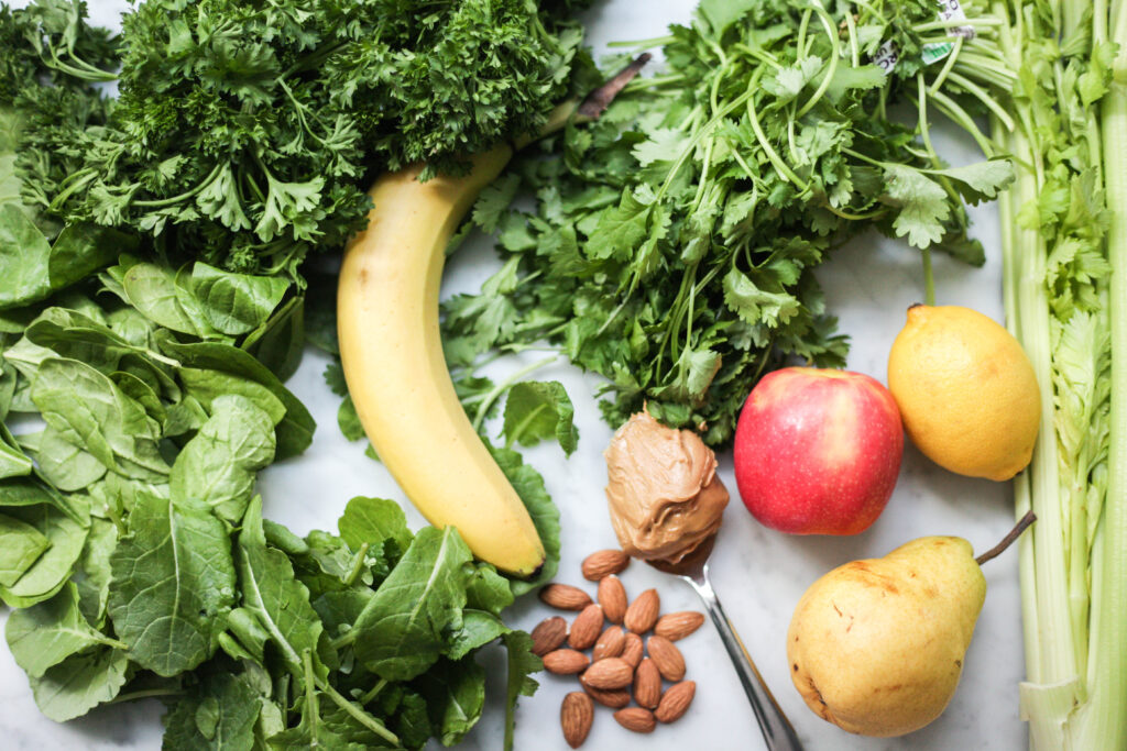 Green smoothie ingredients - leafy greens, banana, apples, pear, lemon and peanut butter