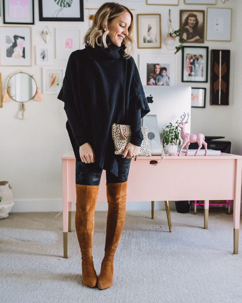 Tan over the knee boots with black poncho and leopard clutch.