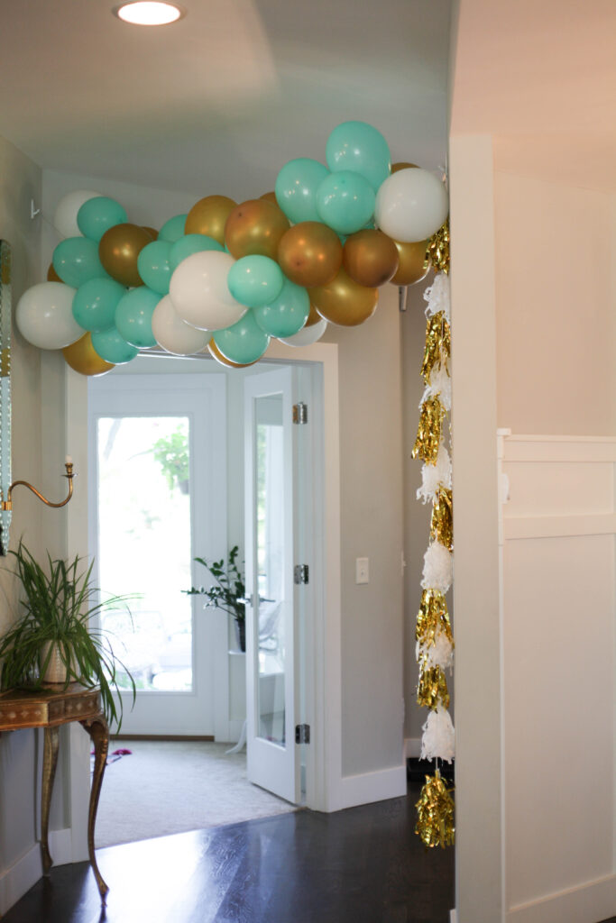 A mint, gold and white balloon arch with tassels.