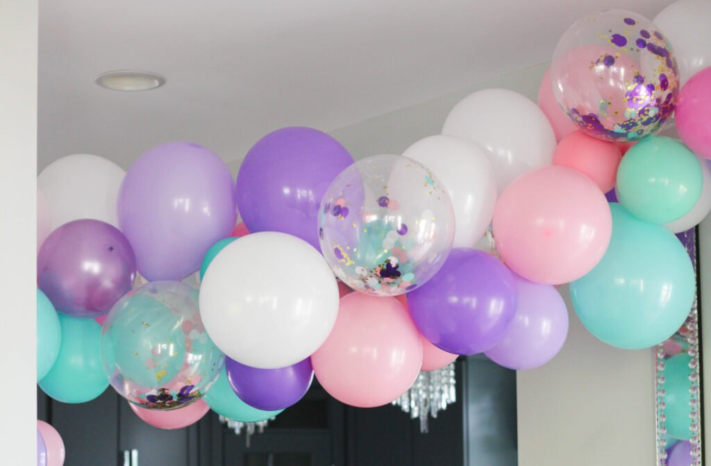 Pink, purple, teal and confetti balloons for a unicorn theme birthday party
