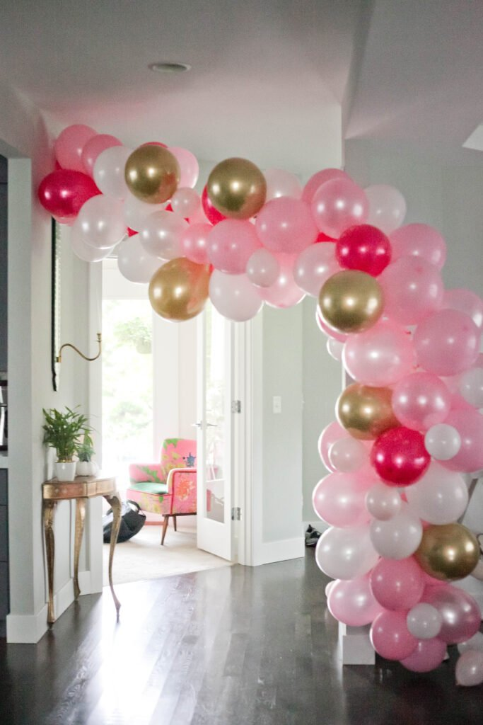 A pink, white and gold balloon arch for a Minnie Mouse birthday for a 2 year old.