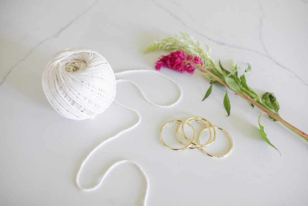 Supplies for making a DIY macrame plant hanger: macrame cord, a ring and a plant.