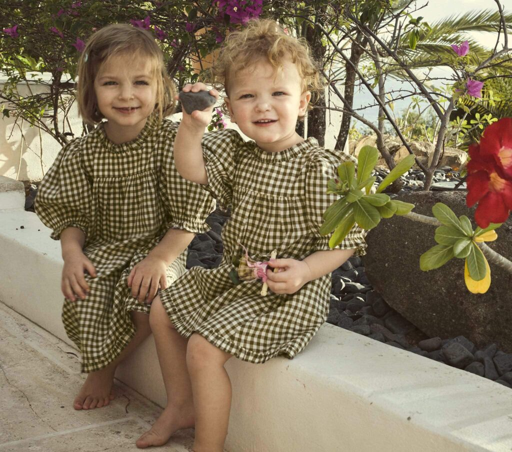 Little girls in matching olive gingham dresses from Doen